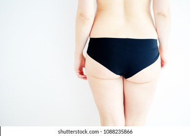 closeup of young womans buttocks with white background