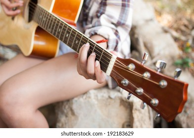 Closeup of young woman's hands playing acoustic guitar outdoors