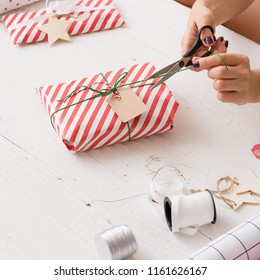 Closeup of young woman's hands wrapping Christmas or birthday gift in striped paper and decorating it with and twine and tag. Girl wrapping presents for the party.