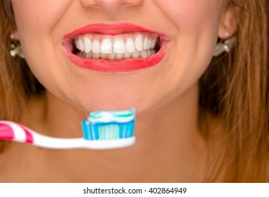 Closeup young womans mouth showing white healthy teeth and holding toothbrush in front.