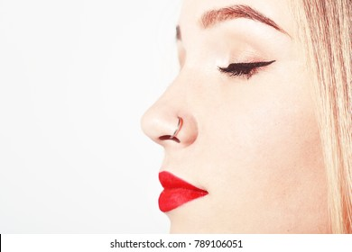 Closeup of a young woman's visage with piercing hanging from her nose.  Beauty Teenager Girl Portrait. Young attractive girl with piercing on her nose. Young girl with red lips and piercing in nose.