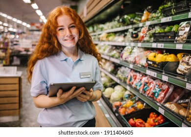Closeup of a young worker with digital tablet in grocery store. Happy trainee working in supermarket.
