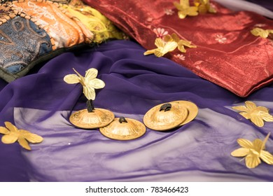 Close-up of zills for bellydancing on a purple veil with arabic cushions