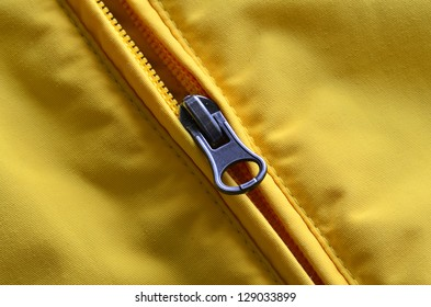 Closeup of zipper on Yellow coat with texture