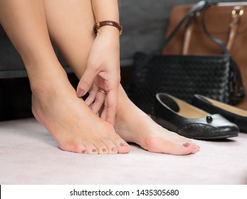Closeup:Bare feet of working woman, she touching her toes to release pain after long day wearing pointy and narrow shoes  -  Medical condition called bunions (Hallux valgus) Woman's health concept.