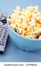 close-ups of bowl of popcorn and remote control