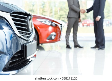 Closing the deal. Selective focus on the car customer shaking hands with dealer on the background