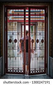Closing door behind Woman closes the iron gate door behind her