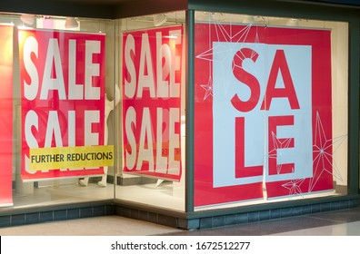 Closing down sale sign with further reductions and discount in shop store mall window