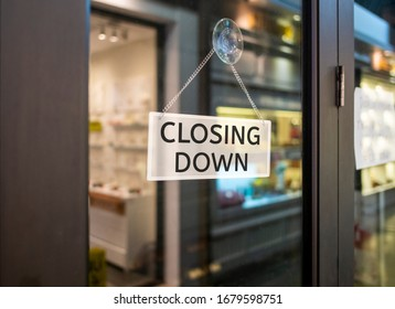 Closing Down sign painted on the window of a dress shop.