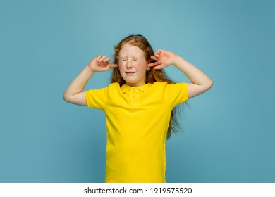 Closing ears. Happy, smiley redhair girl isolated on blue studio background with copyspace for ad. Looks happy, cheerful. Childhood, education, human emotions, facial expression concept.