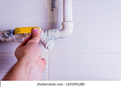 Closing or opening the gas valve. The man is holding his hand on the valve to close the gas supply to appliances such as gas cooker and gas stove. Concept lifestyle.