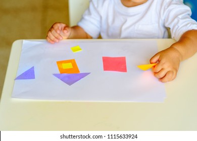 Closse up child hand make applique  glues colorful house, applying color paper using glue while doing arts and crafts in preschool or home. Idea for children's creativity, art project made of paper
