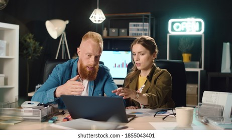 Closup young business couple discussing project results in night office. Young man and woman working overtime in hipster office. Focused business people looking laptop screen indoors