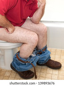 Closupe of a man thinking things over while sitting on the toilet.