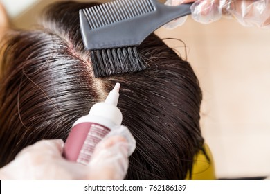 Closu-up of hair dresser applying chemical hair color dye onto hair roots in salon