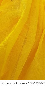 Cloth. Coarse fabric. Yellow textile surface. Mesh background. Wavy folds of fabric. Vintage background