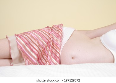 A cloth covers part of a pregnant woman lying on her side.