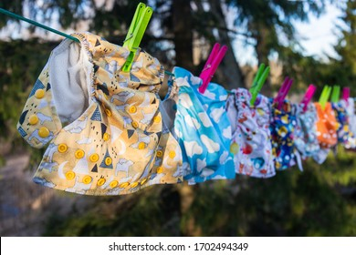 Cloth diapers dry in the sun on a full clothesline - laundry day! Reusable baby diapers in front of a nature background and blue sky. Eco friendly nappies, Sustainable lifestyle. Zero waste concept