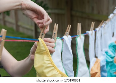 Cloth Diapers on a Clothesline - It is laundry day! A mom hangs cloth diapers on a clothesline to dry in the sun.