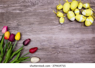 cloth multicolored tulips and tellow easter egg on wood