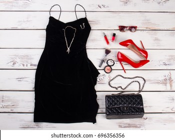 Clothes Accessories fashion Set. Black dress and red heels, modern party accessories on wooden background.