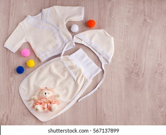 Clothes for babies. Clothes for children from soft beige fabric. Baby's loose jacket, cap and envelope for legs wear for baby fleece. Teddy bear in a pink dress to create tenderness.