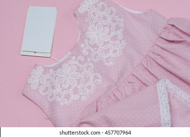 Clothes for baby girl on pink background. Copy space for text
