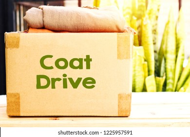 clothes in carton box on wood table for donation, coat drive concept