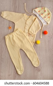 Clothes for the child from soft fabric. Clothes for the baby are yellow on a wooden background. View from above. Pants, baby's loose jacket, cap made of soft fabric. Warm clothes for babies.