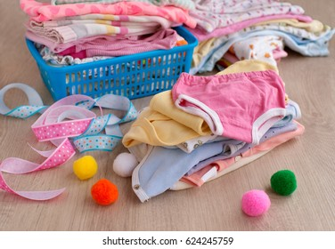 Clothes for children in a pile. Clothing for children and babies folded in a pile on the table. Clothes for the child in the laundry basket. Romper suit and baby's loose jacket made of soft fabric.