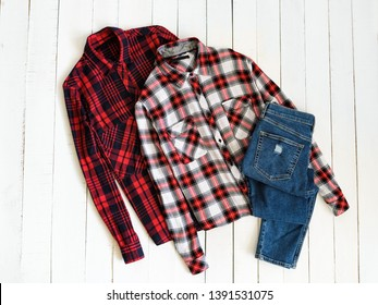 Clothes concept. Two checkered shirts and jeans on a wooden background. Top view