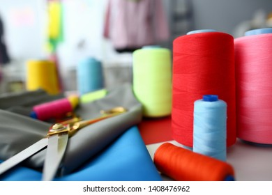 Clothes Designing Tailor Craftsmanship Concept. Fabric and Sewing Tools on Table. Needle Machine Bobbins Spools of Color Thread with Gold Scissors on Silky Textile. Designer Workplace