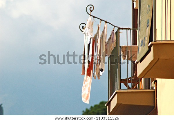 Clothes drying hanging off of a balcony in Gaeta, Italy in the late summer afternoon
