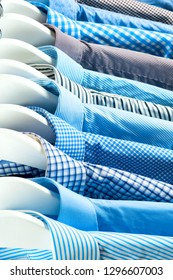 Clothes hang on a shelf . Cloth Hangers with Shirts. Men's business clothes. Fashion