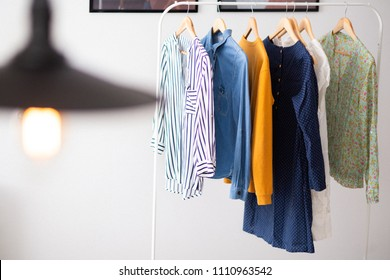 Clothes hang on wooden coat hangers in clothing store with home tone. Shopping and spending concept