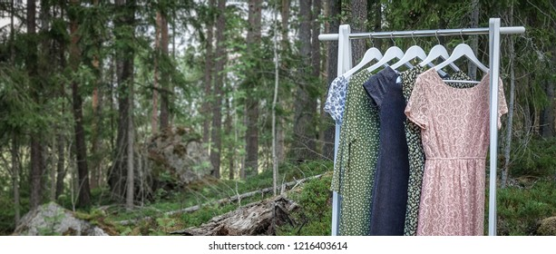 Clothes hanger with dresses in the woods. Concept for organic, recycled clothes and eco-friendly, ecological fashion.