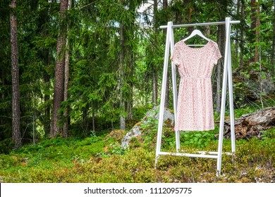 Clothes hanger with a pink dress in the forest. Concept for organic clothes, eco-friendly, ecological fashion.