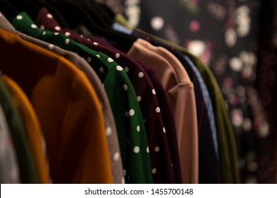 a lot of clothes hangers that are closely located next to each other in a store with women's clothing, an atmosphere of women's space with a large selection of colorful clothes, noise effect