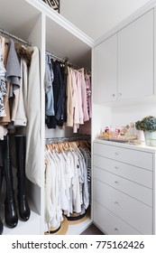 Clothes hanging in a luxury walk in wardrobe
