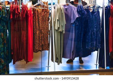 Clothes hanging on the rack in the fashion store. Woman choosing and buying clothes in shopping store. Retail shopping.