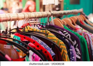 Clothes hanging on a rail at a street market outdoors