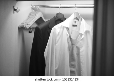 Clothes hanging on rail in wooden closet at home, wardrobe with shirts hanging on rail. Business concept