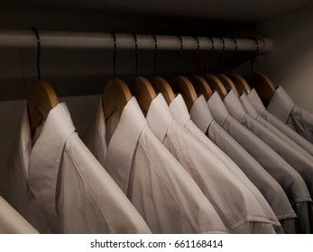Clothes hanging on rail in wooden closet at home, wardrobe with shirts hanging on rail