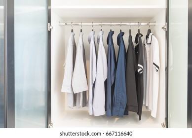 clothes hanging on rail in wooden white wardrobe, interior design concept