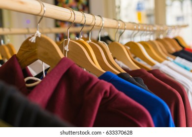 Clothes hanging on a rails in a wardrobe