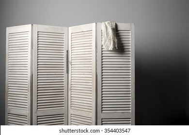 clothes hanging on the white folding screen on a gray background