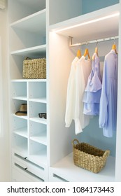 Clothes hanging in white wooden  wardrobe