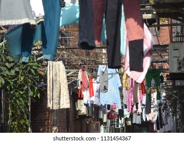 Clothes have been hung to dry across a back street in Shanghai. Air conditioning units and brick walls can also be seen.