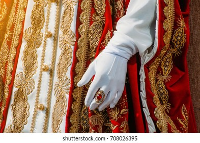 Clothes of a historical imperial woman with red elements, a hand in white gloves and a ring with a precious stone